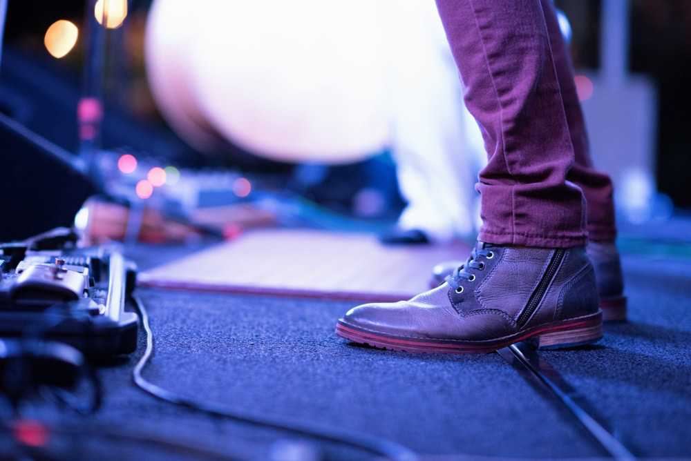 musicans legs, on stage, with a effects pedal board